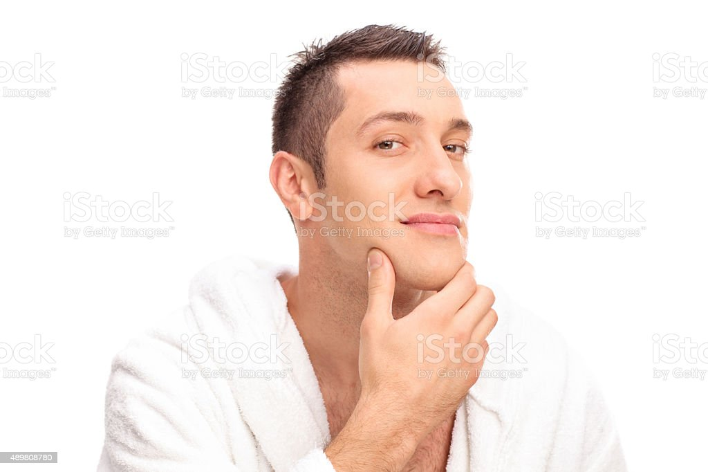 Freshly shaved young man in a white bathrobe stock photo