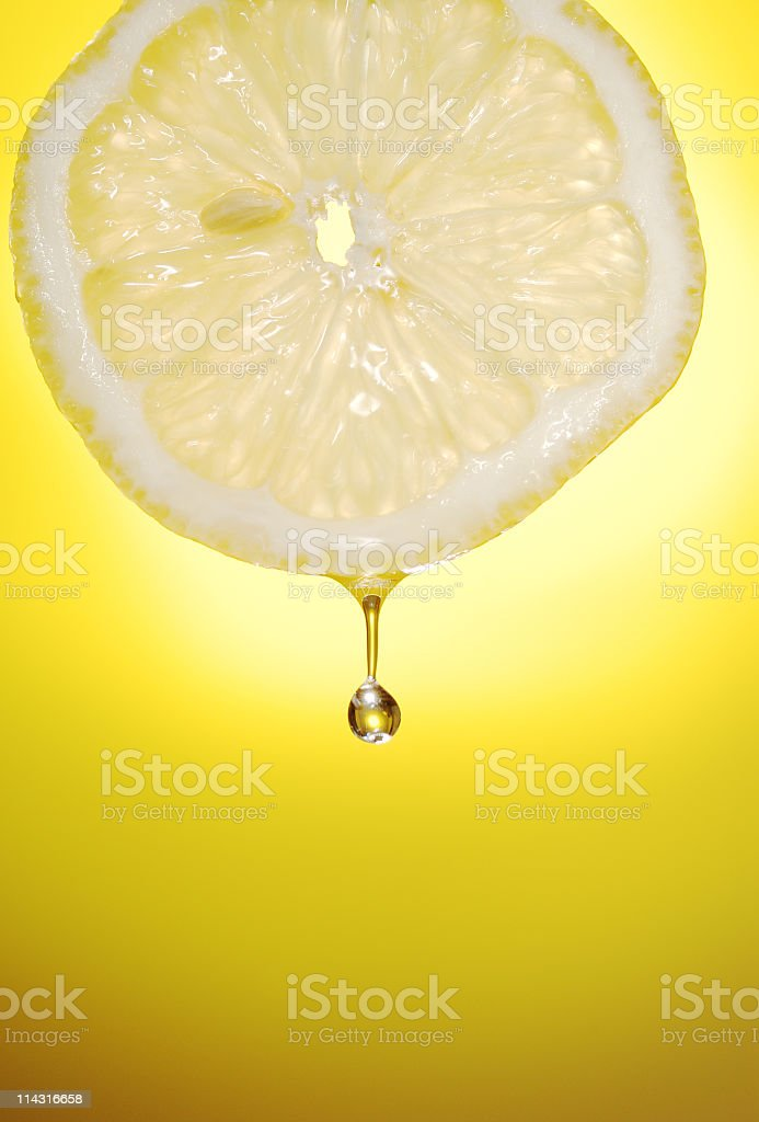 Freshly sliced lemon with a drop of water coming off it stock photo