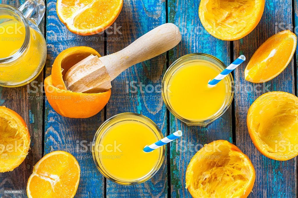 freshly squeezed orange juice in a glass with straws stock photo