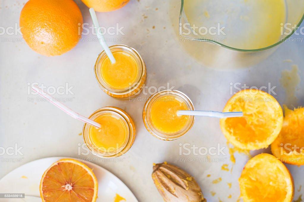 Freshly squeezed orange juice in jars with drinking straw stock photo