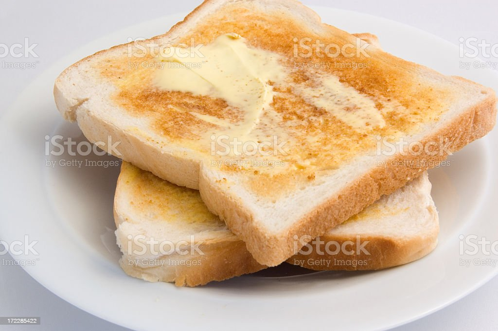 Freshly toasted bread smothered in creamy butter stock photo