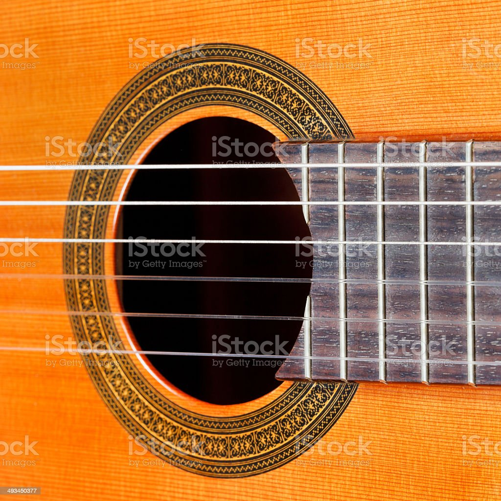 fretboard and sound hole of acoustic guitar stock photo