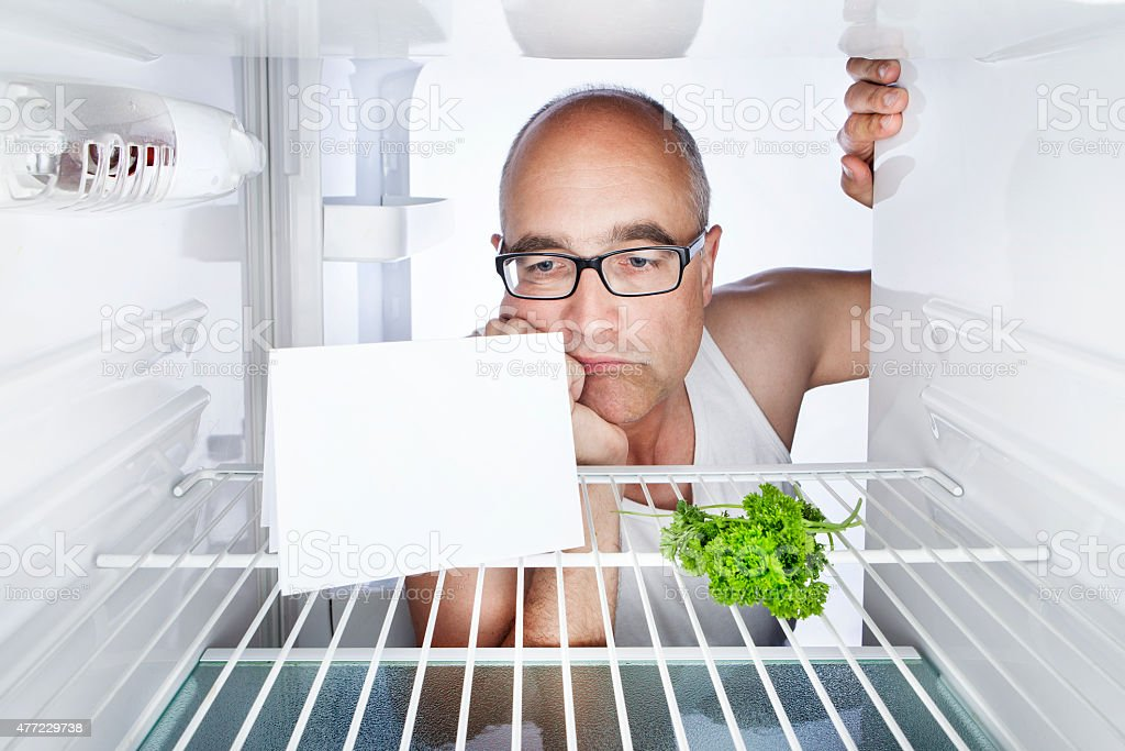 Fridge disappointed middle-aged man blank card copy space stock photo