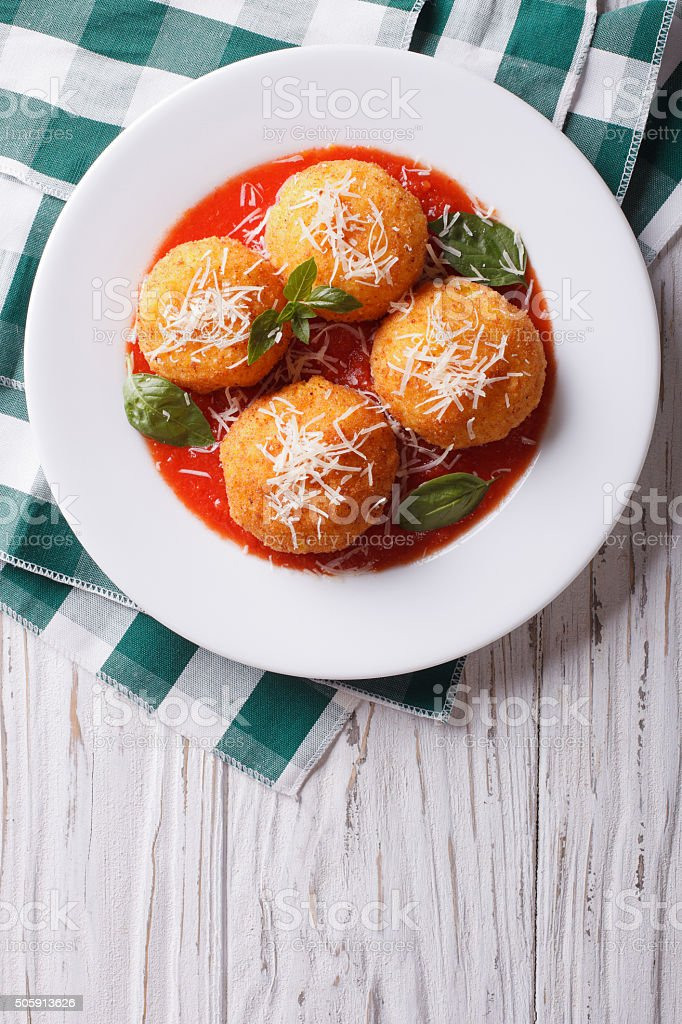 fried arancini rice balls with tomato sauce. vertical top view stock photo