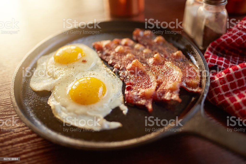 fried bacon and eggs in iron skillet stock photo
