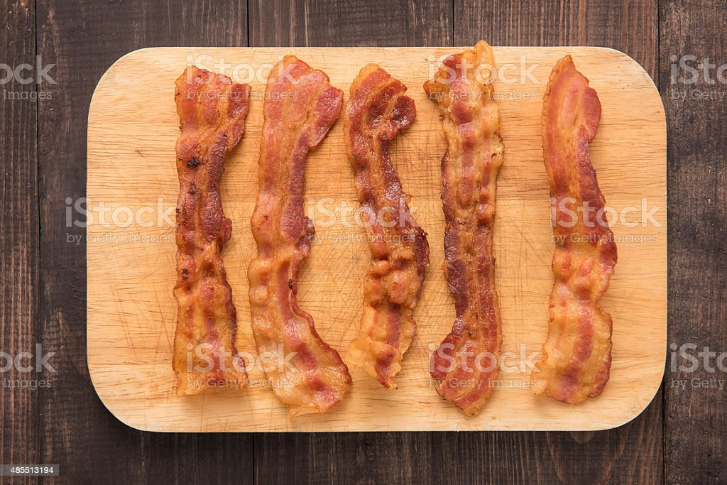 Fried bacon strips on the wooden board stock photo