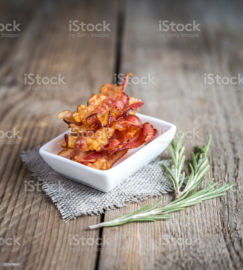 Fried bacon strips with fresh rosemary stock photo