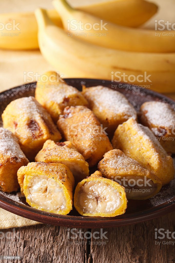 Fried bananas sprinkled with powdered sugar close-up. Vertical stock photo