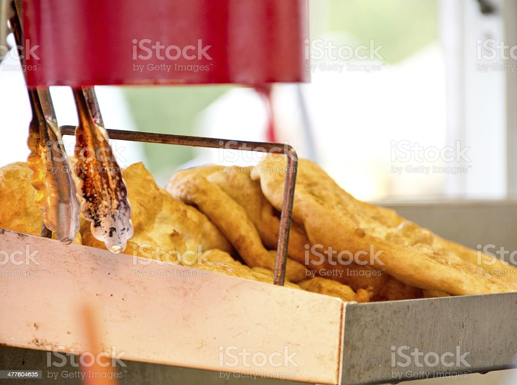 Fried bread and tongs under a heat lamp stock photo