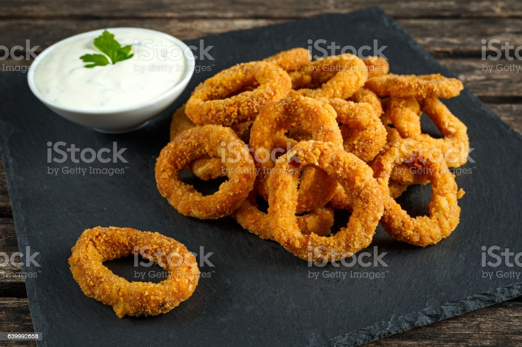 Fried Breaded Onion Rings with sauce on stone board stock photo