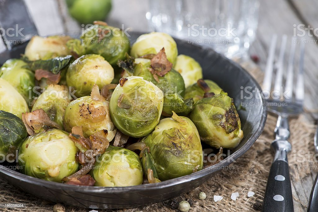 Fried Brussels Sprouts in metal dish next to fork on table stock photo