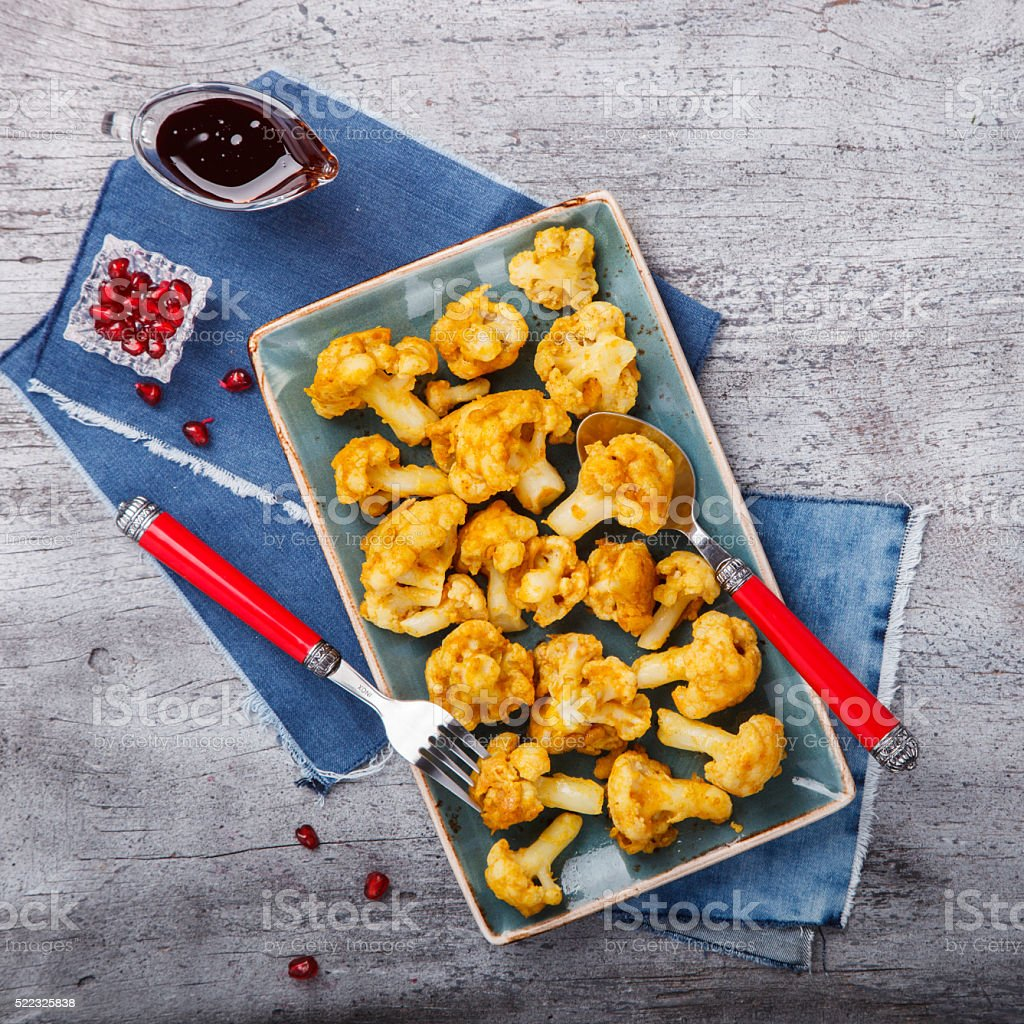 Fried cauliflower in spices with pomegranate sauce stock photo