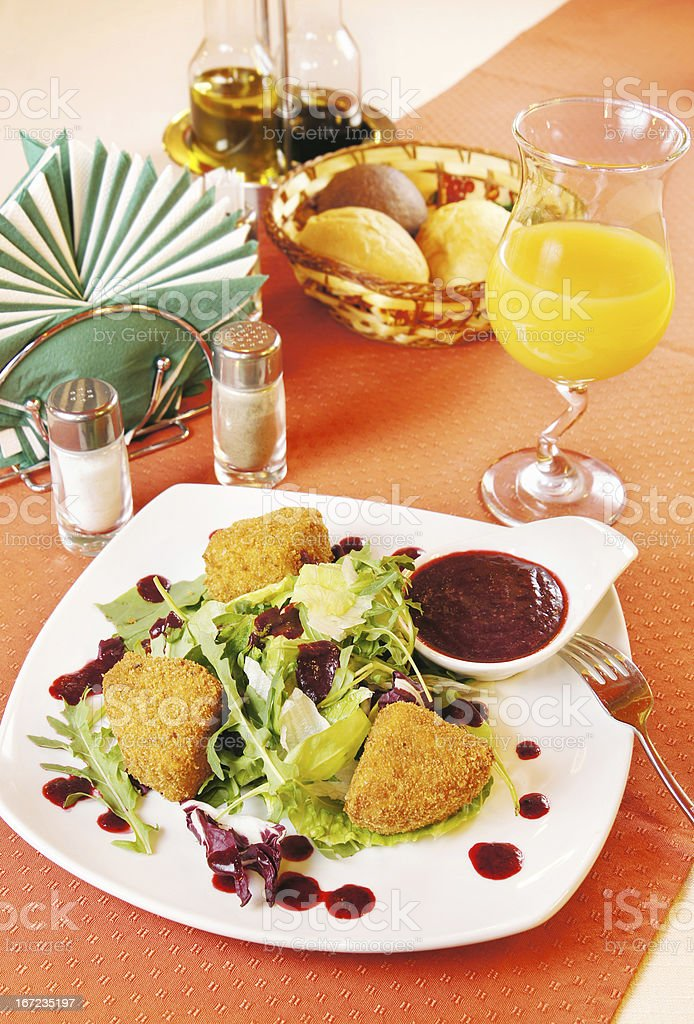 Fried cheese Camembert with cranberry sauce on a laid table royalty-free stock photo