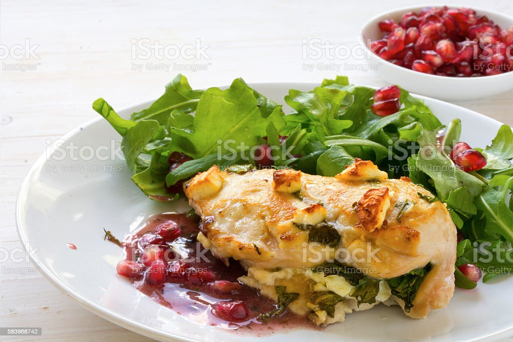 fried chicken breast, feta cheese, arugula and pomegranate stock photo
