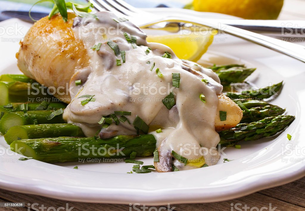 Fried chicken breast on asparagus with tarragon and mushroom sauce stock photo