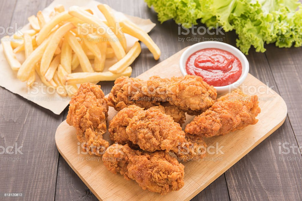 Fried chicken drumstick and french fries on wooden table stock photo