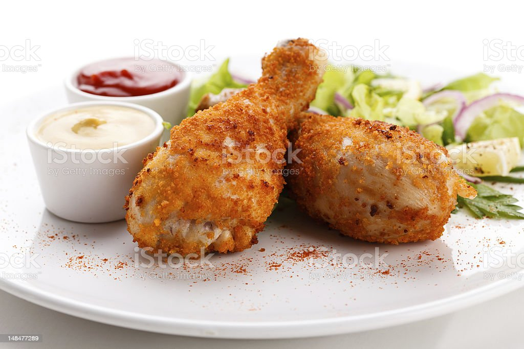 Fried chicken drumsticks and vegetables royalty-free stock photo