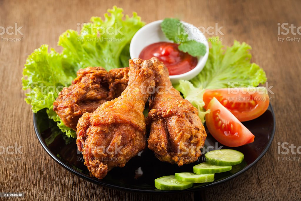 Fried chicken drumsticks and vegetables stock photo