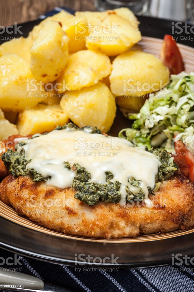 Fried chicken fillet with spinach and cheese. stock photo