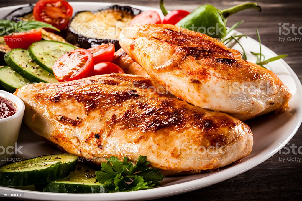Fried chicken fillets and vegetables on wooden background stock photo