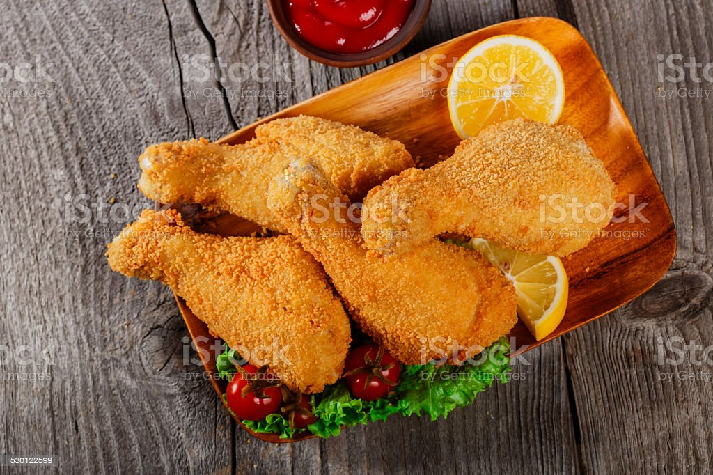 fried chicken leg in breadcrumbs on a wooden surface stock photo