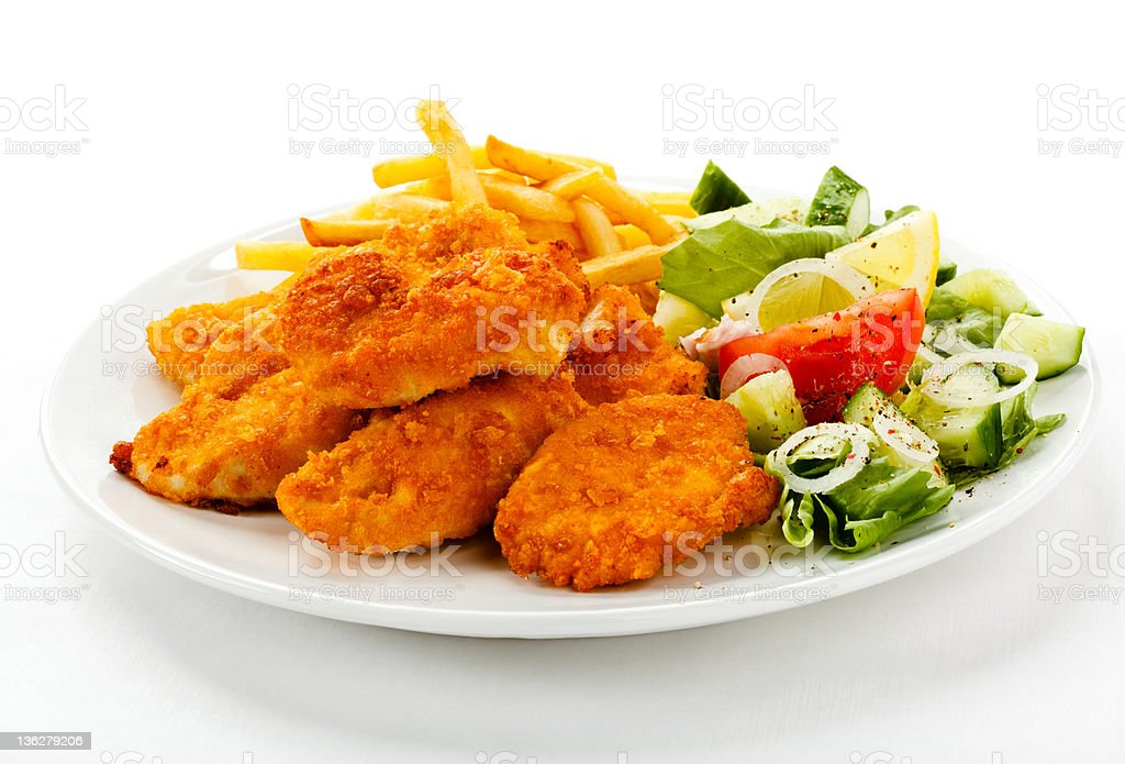 Fried chicken nuggets, French fries and vegetables royalty-free stock photo