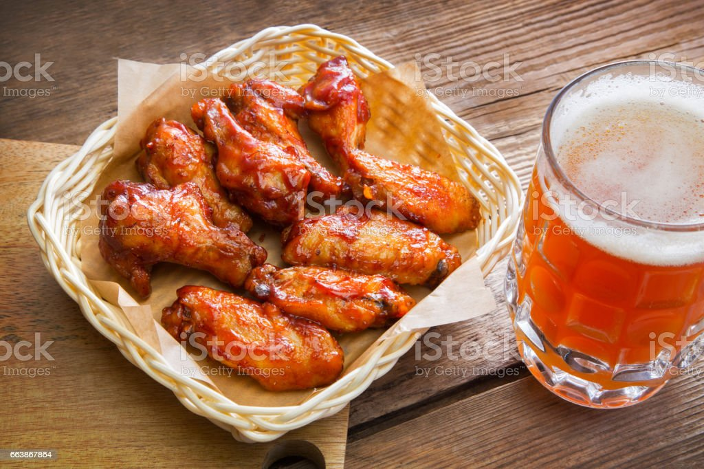 Fried chicken wings and a large mug of beer stock photo