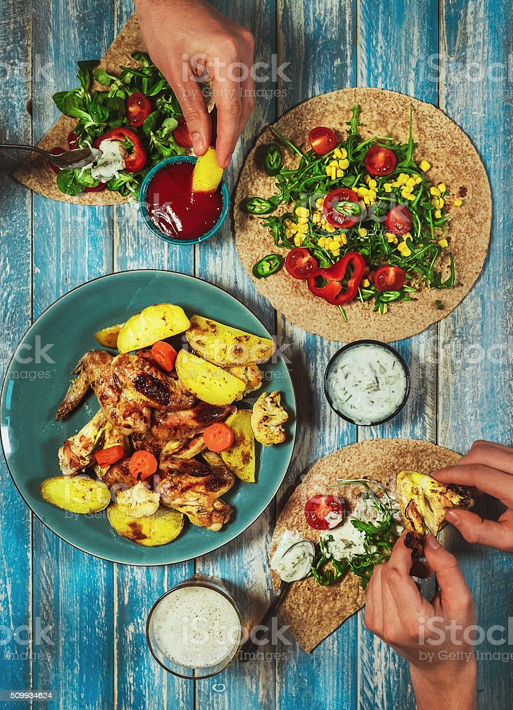 Fried chicken wings with vegetable salad and taco tortilla stock photo