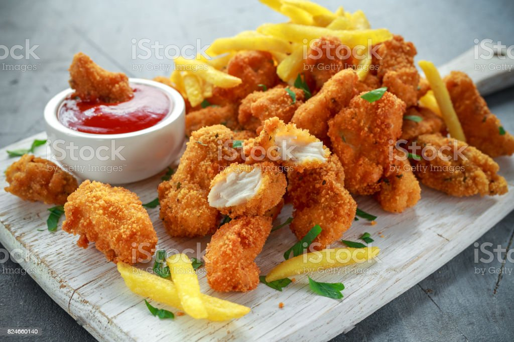 Fried crispy chicken nuggets with french fries and ketchup on white board stock photo