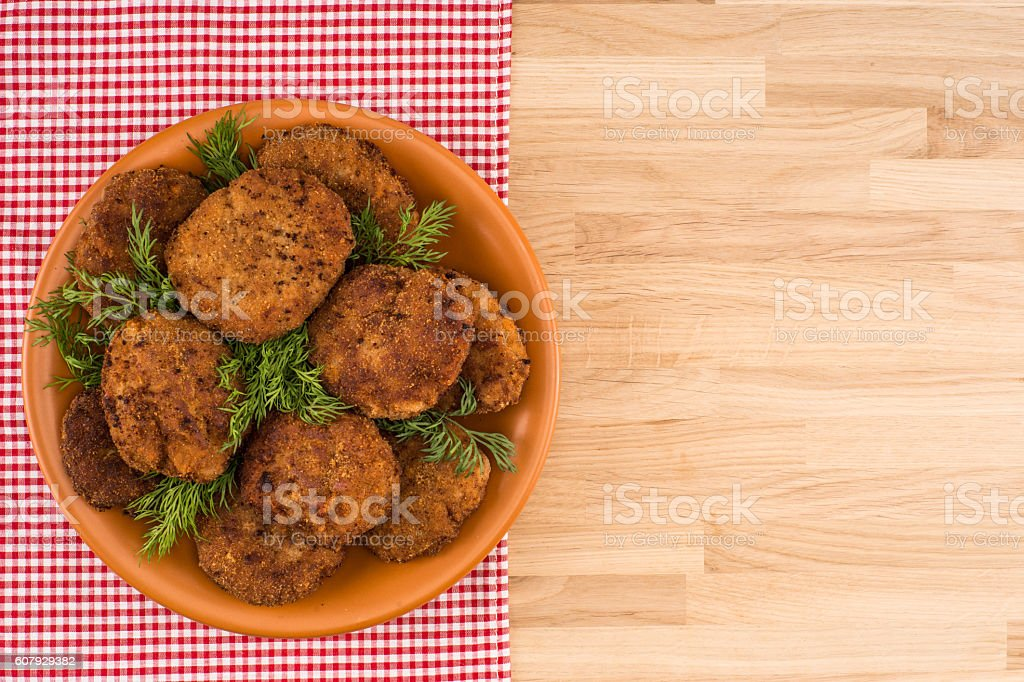 Fried cutlet in the plate on wooden table stock photo
