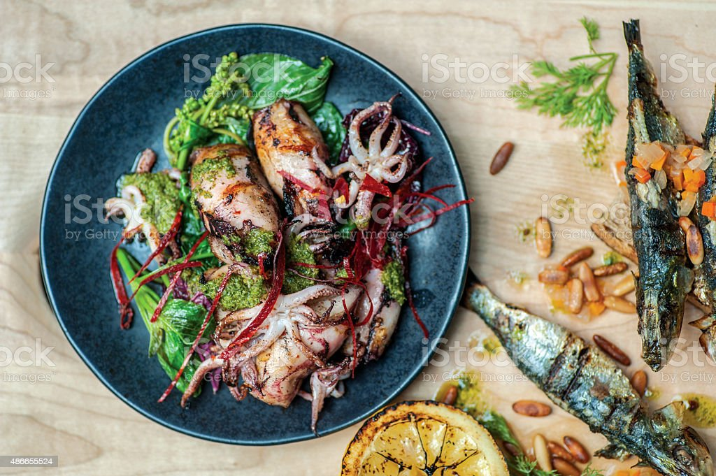 Fried cuttlefish and octopus with chicken breast and vegetables stock photo