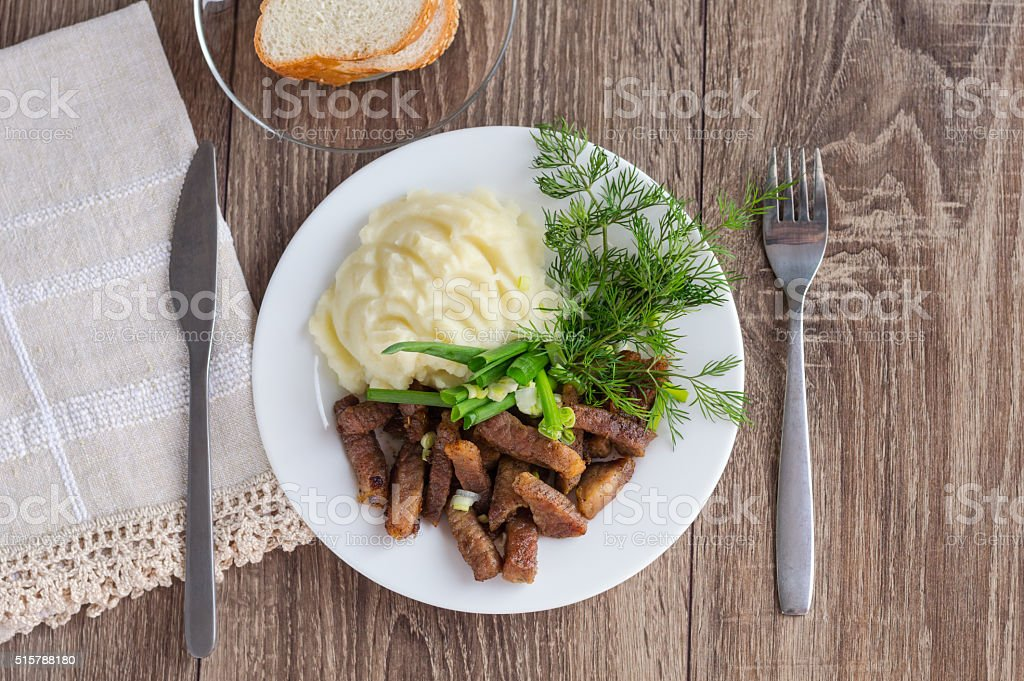 Fried diced pork with onions, mashed potatoes and dill stock photo