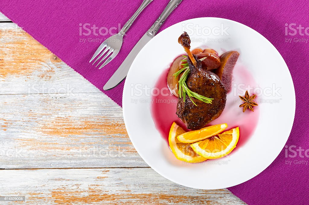fried duck leg in wine with orange and apple slices stock photo
