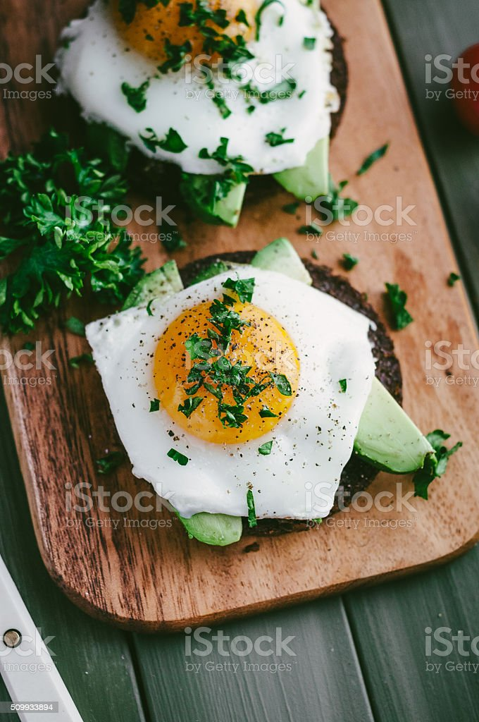 Fried egg and Avocado on bread stock photo