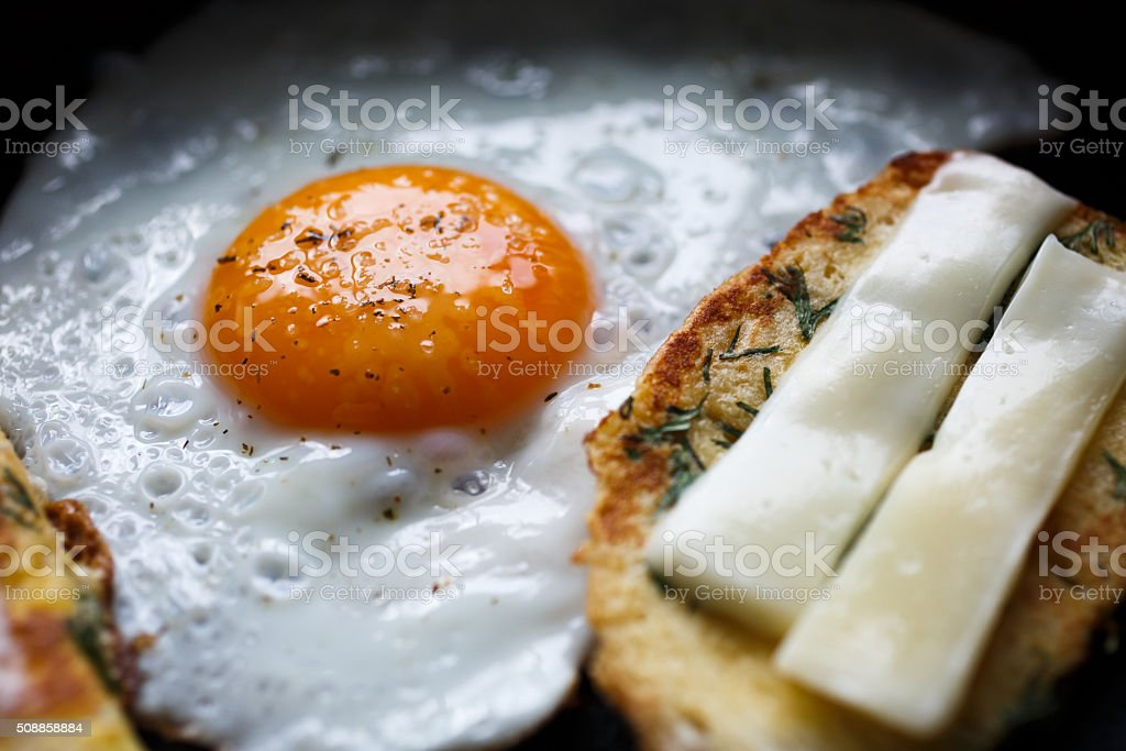 fried egg and bread with cheese on the pan stock photo