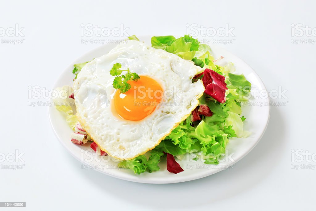 Fried egg and green salad stock photo