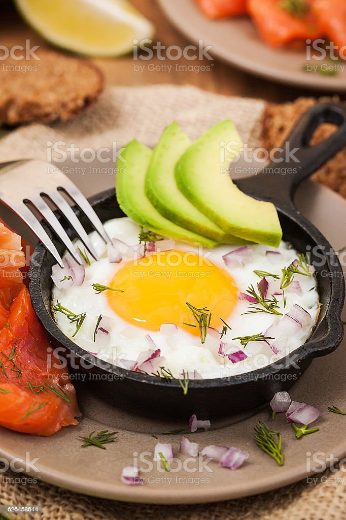 Fried egg, avocado and smoked salmon in frying pan stock photo