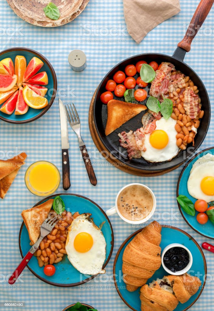 Fried egg, beans, tomatoes, bacon, toast various fruits, juice and coffee on a rustic table, top view stock photo