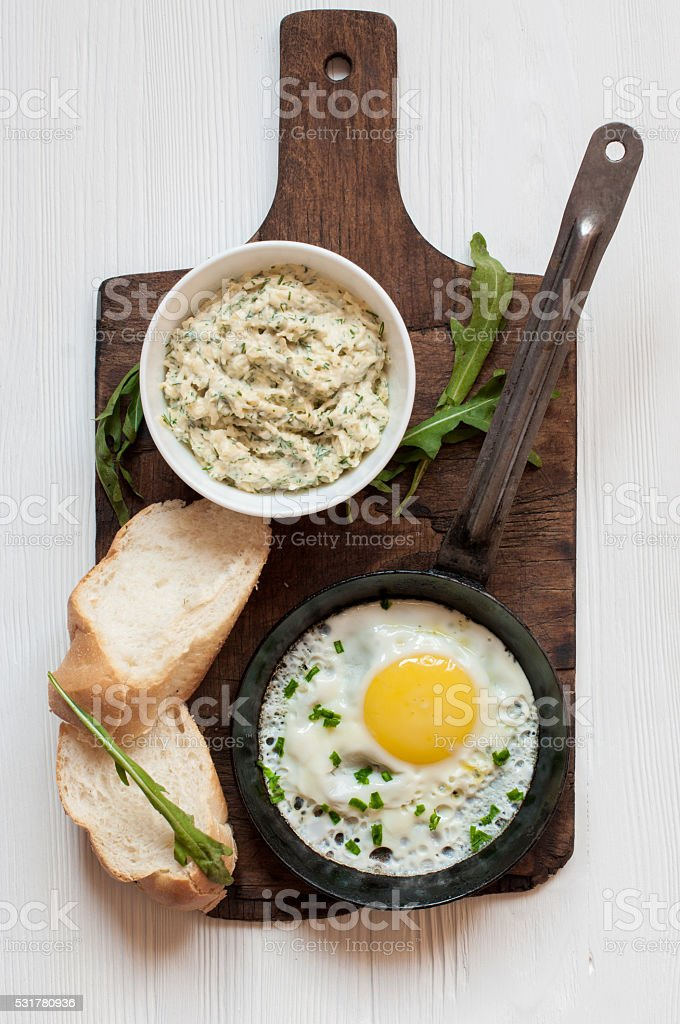 Fried egg, cheese sauce, loaf and arugula stock photo