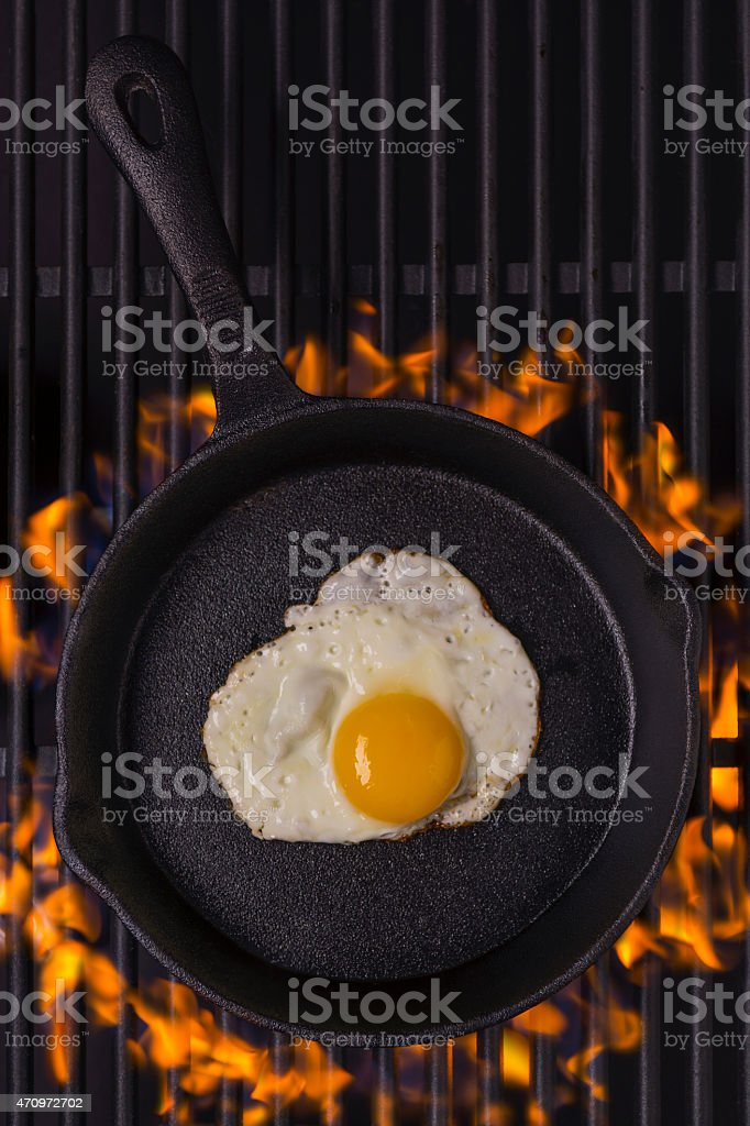 Fried egg on a flaming grill from above stock photo