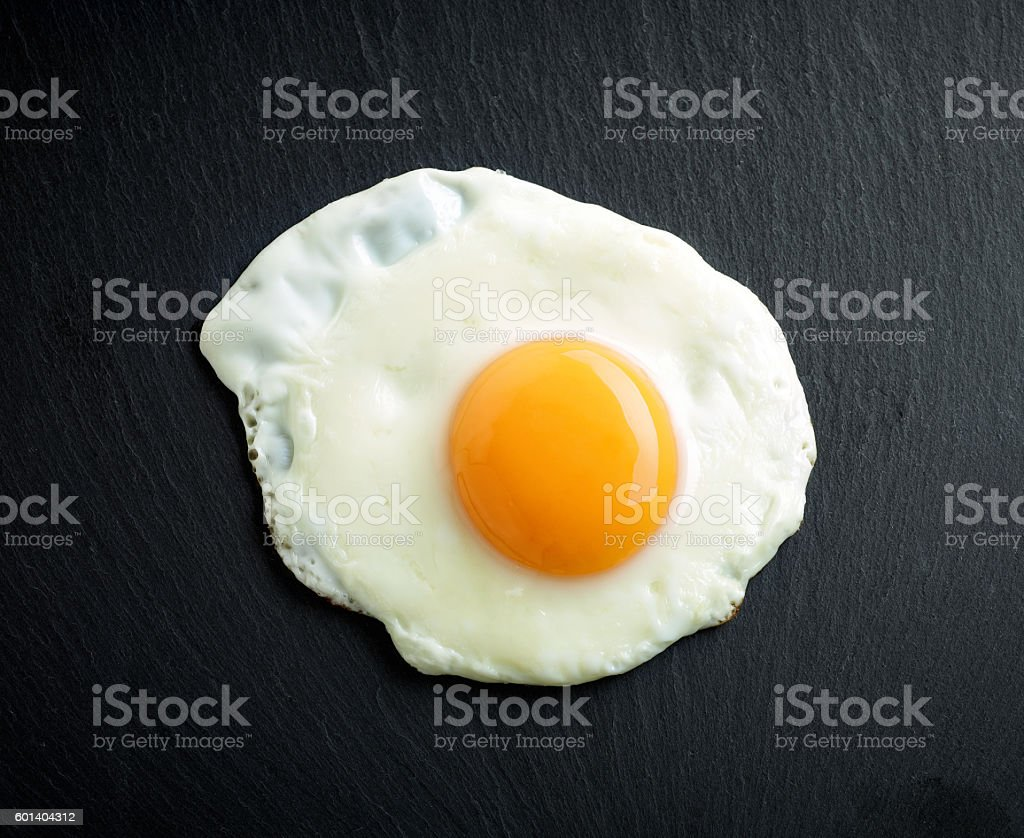 fried egg on black background stock photo
