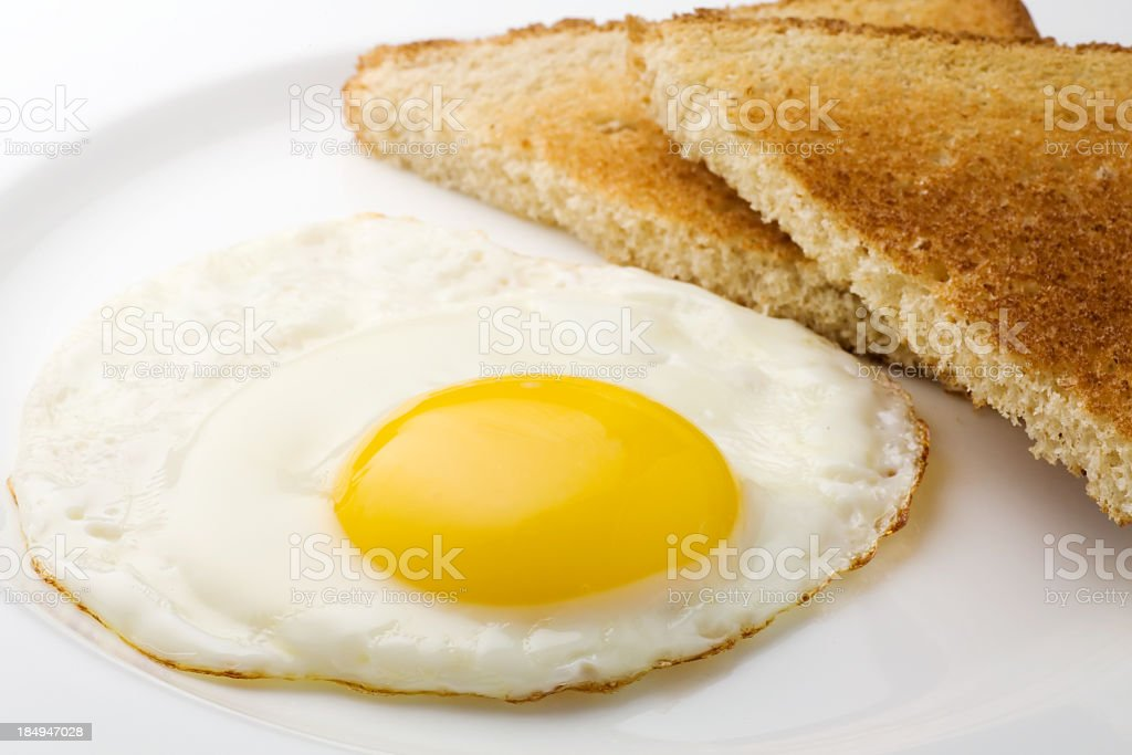 Fried egg sunny side up and plain sliced toast stock photo