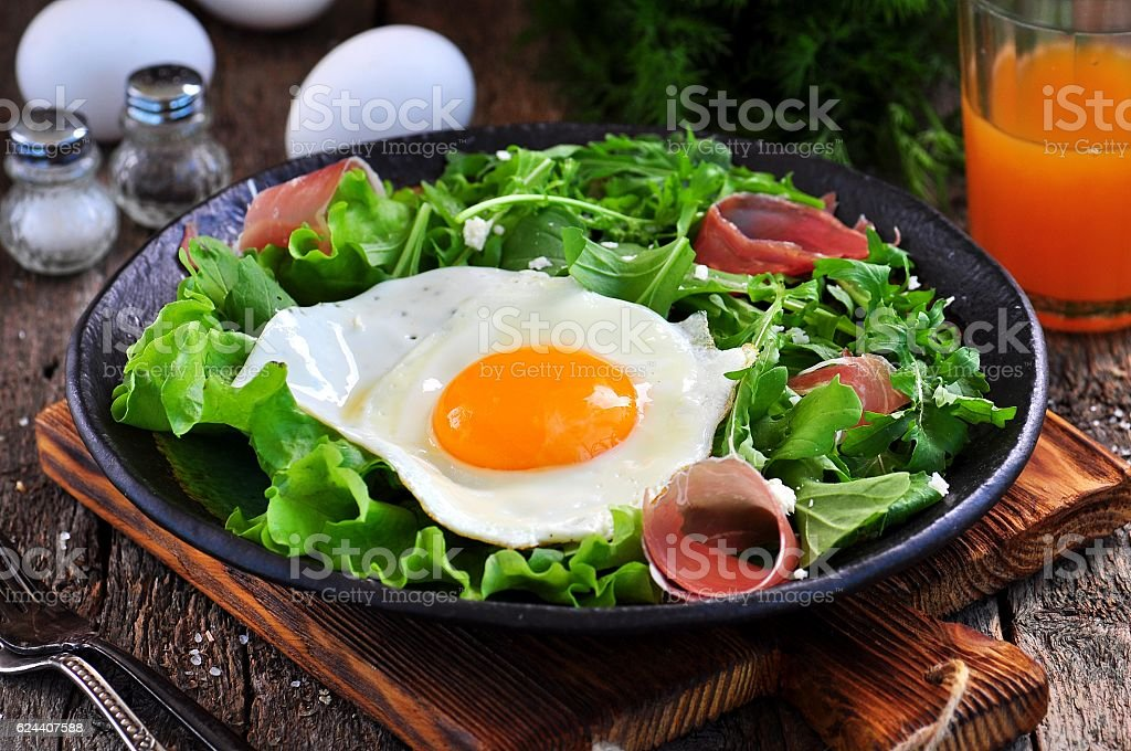 Fried egg with lettuce, arugula, parmesan and jamon. Rustic food. stock photo