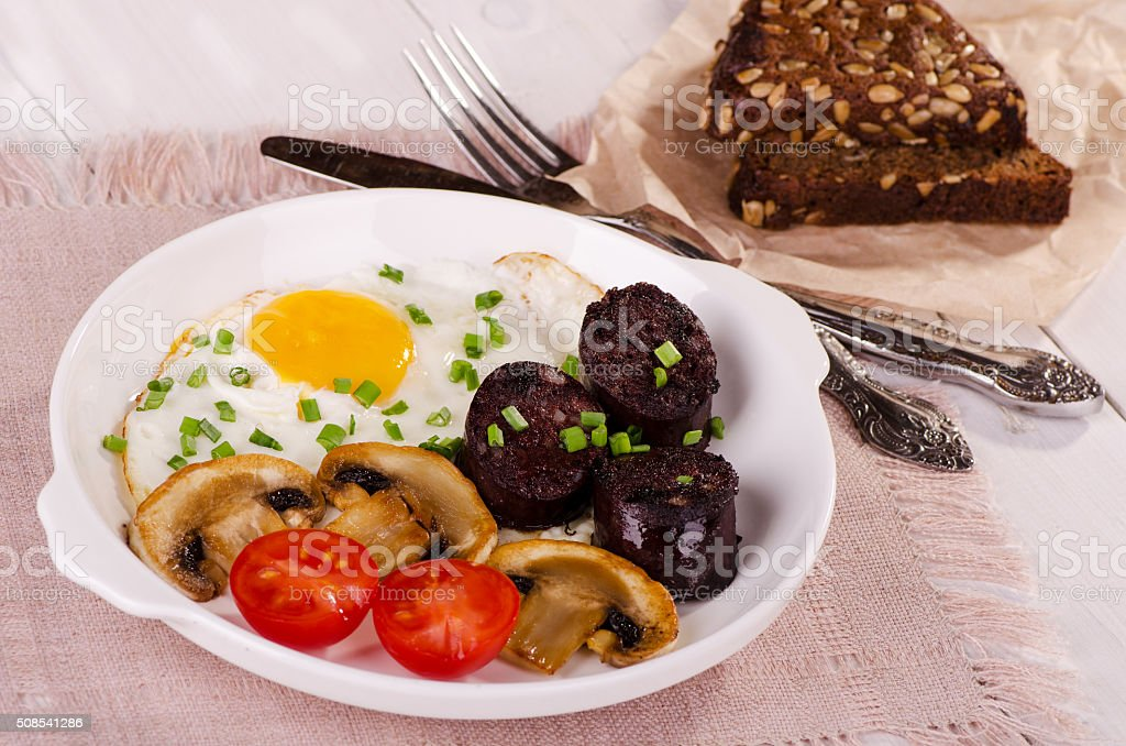 fried egg with mushrooms, tomatoes and black pudding stock photo
