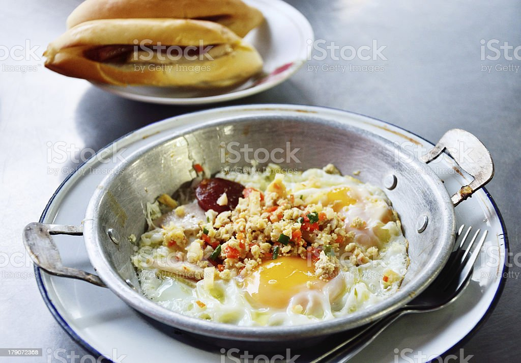Fried egg with pork and sausage in hot pan royalty-free stock photo
