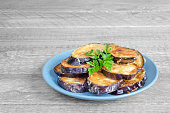 Fried eggplant, on the plate and a gray wooden background
