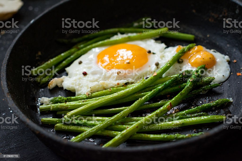 Fried eggs and asparagus in skillet stock photo