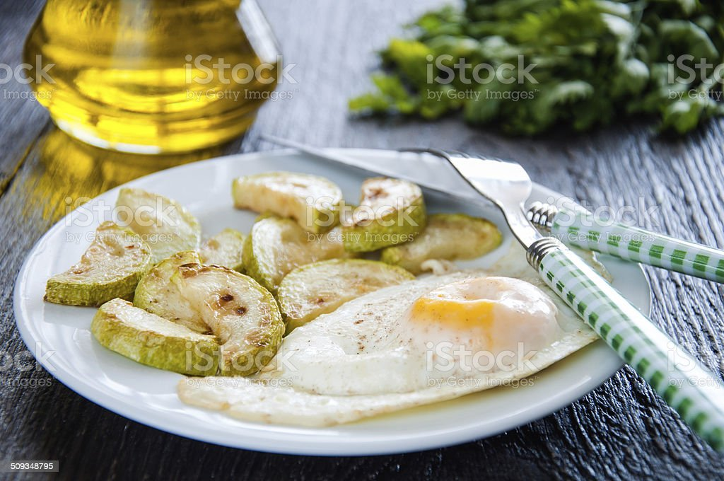 fried eggs and chopped zucchini with parsley on the plate stock photo