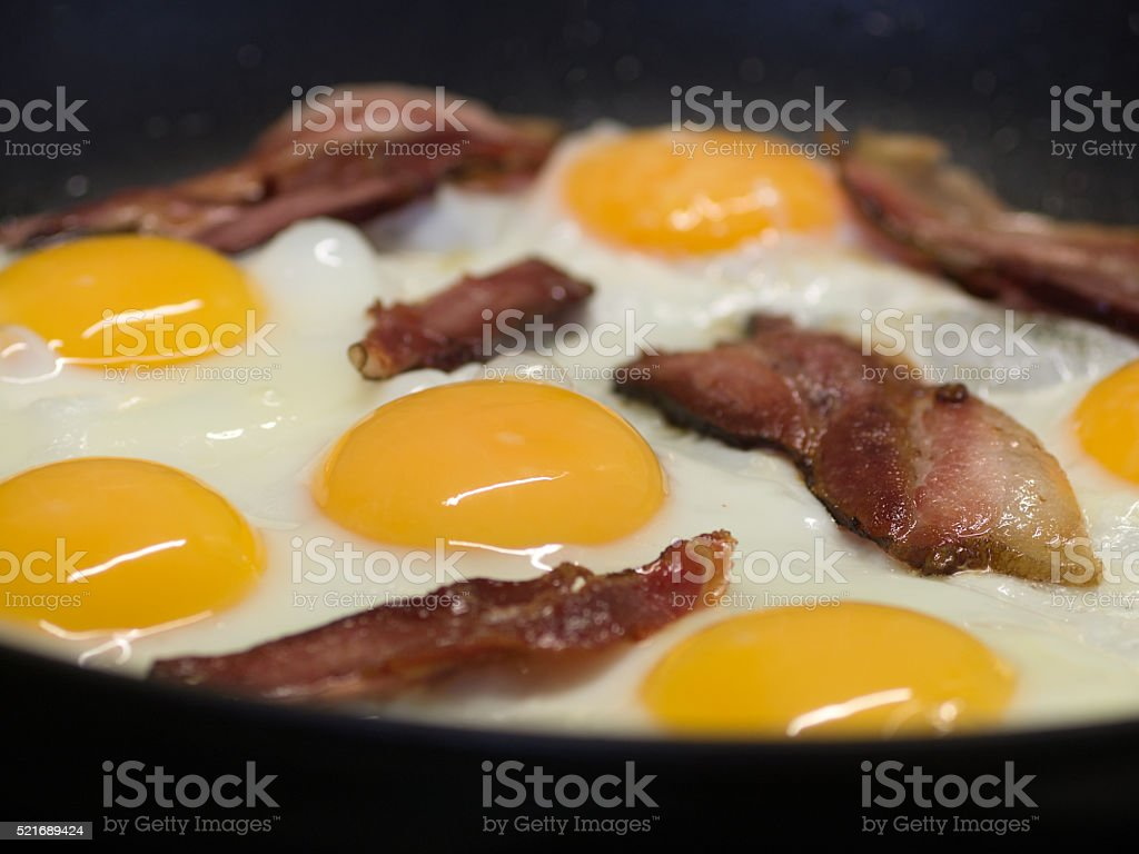 Fried eggs and pork bacon rashers in pan royalty-free stock photo