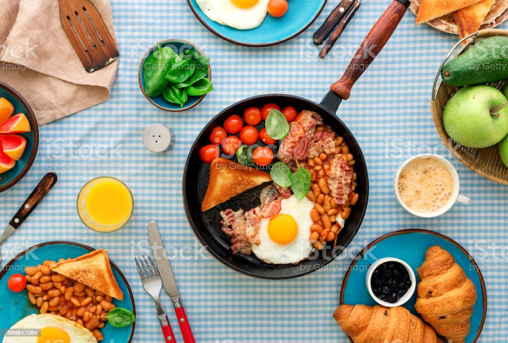Fried eggs, bacon, tomatoes, beans and spinach in a frying pan on a table with various fruits and croissants stock photo